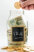 picture of retirement  - Caucasian hand putting gold coin into glass jar on white background with black chalk label or panel and used for saving US dollar bills for retirement in IRA precious metal fund - JPG