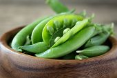 picture of pea  - Some colorful green pea pods in wooden bowl on rustic background - JPG