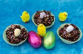 picture of baby easter  - Looking down on a perfect Easter collection of Easter eggs chocolate cornflake cakes and little baby yellow toy chicks - JPG