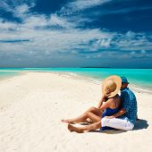 pic of couple sitting beach  - Couple in blue on a tropical beach at Maldives - JPG