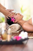 stock photo of thai massage  - young woman receiving head massage in spa environment - JPG