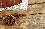 foto of chocolate spoon  - Bar of chocolate in foil with coffee beans in spoon on wooden background - JPG