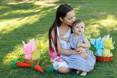 pic of baby easter  - Teen girl kissing happy baby sister on green grass in park with wicker basket with chocolate eggs for Easter holiday. Selective focus