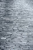 stock photo of cobblestone  - Dark wet cobblestone road with reflection after rain - JPG