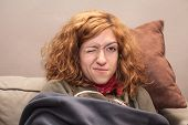 pic of redhead  - Closeup of a redhead woman face with one eye closed relaxing on the sofa at home - JPG