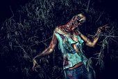 stock photo of bloody  - Horrible bloody zombie girl standing outdoor - JPG