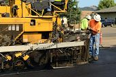image of paving  - Asphalt paving machine laying down a fresh layer of paving on a new road interchange project - JPG