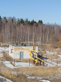 stock photo of gas-pipes  - small gas station with valves and pipes which are gas painted yellow paint is behind the fence in the forest in the early spring and the snow melts around - JPG