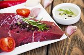 foto of beef shank  - Fresh beef steak on plate with aromatic spices and sauce on a wooden background - JPG