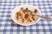 stock photo of pecan  - A bowl of hot fresh cooked oatmeal with pecans and cinnamon  - JPG