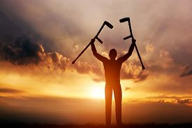 pic of handicapped  - A disabled man raising his crutches at sunset - JPG