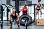 Three muscular athletes lifting and jumping at the crossfit gym poster