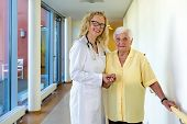 image of nurse  - Young Female Nurse and her Elderly Woman Patient Smiling at the Camera While Standing at the Hallway Inside the Nursing Home - JPG