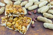 image of hazelnut  - Honey bar with peanuts almonds and hazelnuts surrounded by bunch of roasted and raw peanuts placed on a wooden board - JPG
