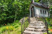 image of stone house  - stone stairs with wrought iron railing curve up to Art Deco style stone house on hill - JPG