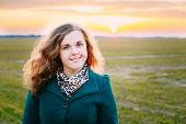 pic of plus size model  - Portrait Of Beautiful Plus Size Young Woman In Blue Coat Posing In Field Meadow At Sunset Background - JPG