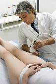 caucasian woman receiving laser treatment at the leg from a male doctor