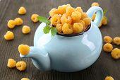 stock photo of teapot  - Yellow raspberries in teapot on wooden background - JPG