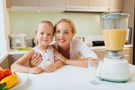 foto of blender  - Portrait of smiling mother and daughter next to blender with healthy drink in a kitchen - JPG