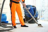 Dry cleaners employee removing dirt from carpet in flat poster
