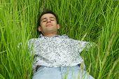 Boy Relaxing In High Green Grass