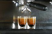 Two shots of espresso being drawn from a professional espresso machine.