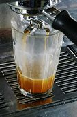 Double latte being extracted from a professional espresso machine - docus on bottom of glass.