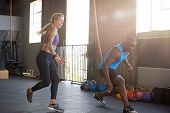 Man and woman sprinting in gym for intense training session poster