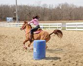 foto of barrel racing  - A young woman races to the finish after rounding a barrel