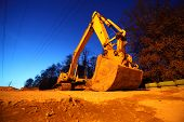 picture of night crawler  - Big yellow crawler tractor with big bucket on yellow sands at night - JPG
