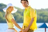 Joyful young couple on the riverboard background