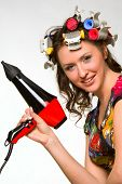 Nice girl with colorful hair-curlers and hair-drier