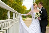 Colorful wedding shot of bride and groom standing on the bridge