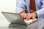 Handsome young businessman bound to laptop with handcuffs
