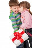 Little girl kissing a boy with gift box