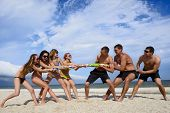 Tug-of-war between girls and guys on the beach