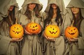 stock photo of nun  - Four nuns with halloween pumpkins in their hands - JPG