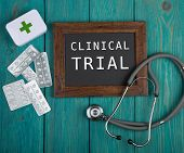 Blackboard With Text clinical Trial, Pills And Stethoscope On Blue Wooden Background poster