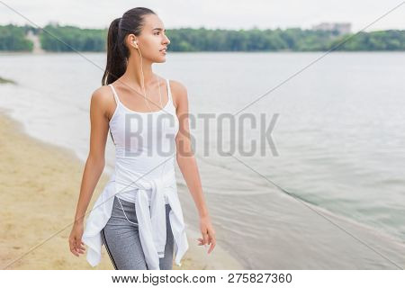 poster of Fitness Motivation. Athlete Female Fit Girl Runner Jogging And Running On Beach Lake In Park. Woman
