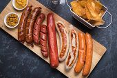 Grilled german sausages with mustard and fried potato chips poster