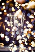 Two Glasses Of Champagne On Dark Bokeh Background poster
