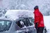 Young Man Is Cleaning Clean Off His Car Of Snow Cover By Brush. Snow Covered Car. Heavy Snow Cleanin poster