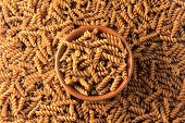 Top View Wholemeal Pasta. Integral Fusilli Into Bowl Over A Wooden Table poster