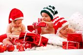 Tres bebés en trajes de Navidad jugando con regalos