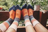 Stylish Socks On Couple Legs And Metal Cup On Wooden Porch With View On Woods In Mountains. Happy Fa poster