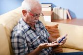 image of blood test  - Senior man doing blood sugar test at home - JPG