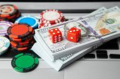 Online Casino Laptop. Laptop Keyboard And Chips With Dice And Money Cash Dollars On Green Gaming Tab poster