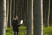 Botanist working with laptop inside a poplar wood