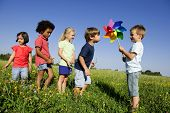 stock photo of windmills  - Children experiencing  alternative energy by blowing at windmill - JPG