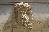 Funny mascaron face on fountain in Alhambra Granada Spain